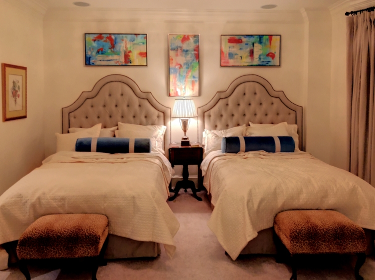 Three abstract paintings framed in a bedroom